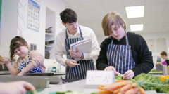 4K Teacher teaching pupils in school cookery class - stock footage