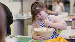 4K Portrait of happy little girl in school cookery class Stock Footage