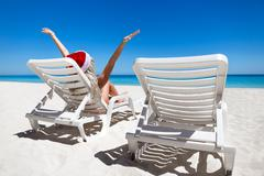 Happy woman in Santa Helper Hat sitting on sunbed with outstretched hands at  Stock Photos