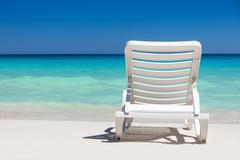 One sunbed on tropical calm beach with turquoise caribbean sea water Stock Photos