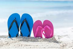 Color slippers on beach Stock Photos