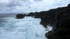 Waves rolling in on black lava coastline in slow motion, big splash. Stock Footage