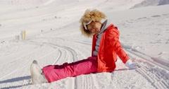 Woman in orange snowsuit sitting on ski slope Stock Footage