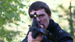 Man runs out of woods and then aiming machine gun at camera Stock Footage
