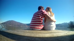 Loving couple giving a kiss on the pier at the lake in the Austrian Alps - stock footage