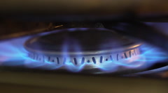 Slow motion macro shot of a gas stove burner lighting Stock Footage