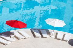 Sun umbrellas and beds near swimming pool at poolside - stock photo