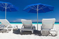 Caribbean beach with blue sun umbrellas and white beds Stock Photos