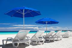 Caribbean beach with blue sun umbrellas and white beds - stock photo