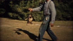1937: Man carries wild opossum animal by tail with girl watching. TRYON, NC - stock footage