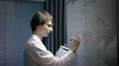 Male scientist writing various high school maths and science formula on Stock Footage