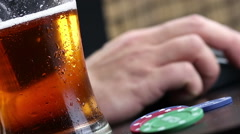 man drink fresh beer with foam in front of mouse and pc keyboard near gamblin - stock footage