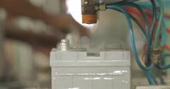 CU and Rack Focus Workers Assembling Automotive Batteries on Conveyor Belt (4K) Stock Footage