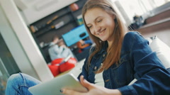 The young girl thumbs through news in the tablet Stock Footage