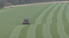 Tractor tows a heavy roller across a field. - stock footage