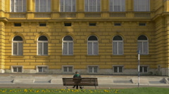 People walking and a woman sitting in front of Croatian National Theatre, Zagreb Stock Footage