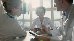 Healthcare, medical: Group of multi-ethnic doctors discuss and looking x-ray Arkistovideo