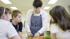 4K Teacher teaching pupils in school cookery class Stock Footage