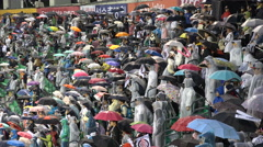 Brave Asian baseball fans defy the pouring rain, sports stadium in South Korea - stock footage