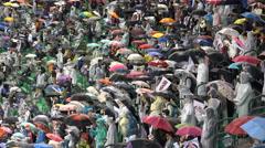 Heavy rain during baseball match, crowd using umbrellas in Seoul South Korea Stock Footage