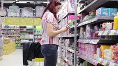 Woman chooses products in store Stock Footage