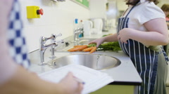 4K Happy little girl washing carrots in school cookery class Stock Footage