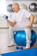 Senior man  holding weights in gym - stock photo