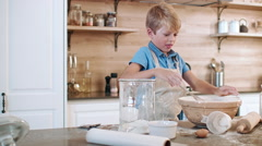 Naughty boy in kitchen making mess - stock footage