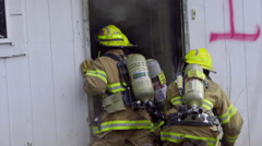 Firefighters crouch at a doorway Stock Footage
