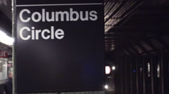 Columbus Circle subway station sign on column with train entering platform in 4K Stock Footage