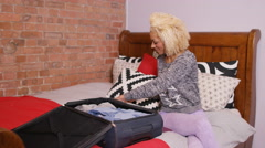 4K Portrait of smiling woman packing luggage in preparation for a trip Stock Footage
