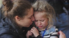 Stock Video Footage of Woman Gives a Hug to Her Daughter Kisses Smiling Little Girl is Crying Kid is