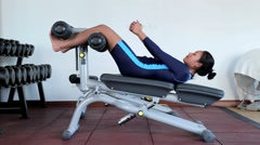 Woman strengthens the abdomen on machine in the gym - stock footage