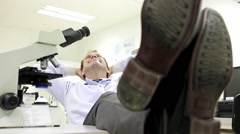 Carefree doctor in lab resting with legs on table Stock Footage