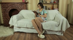 Girl in slippers on the couch reading book in the living room. - stock footage