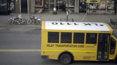 Taxis and school bus driving with parked bicycles on New York City street Stock Footage