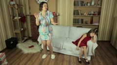 Daughter on the couch watching how dancing and having fun her mother. Stock Footage