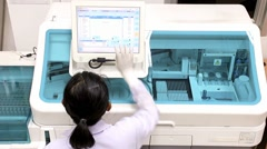 Doctor working in a laboratory on a modern machine for blood testing Stock Footage