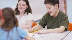 4K Happy elementary school children working at desks in classroom Stock Footage