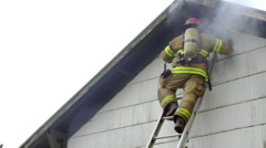 Firefighter looks inside a burning attic Stock Footage