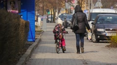 People Mum and Daughter on a City Street Pedestrians Parked Cars Cityscape Stock Footage