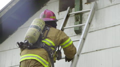 Firefighter climbs ladder to the roof Stock Footage