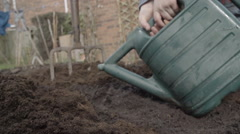 Little Boy Using A Watering Can To Water Seeds Stock Footage