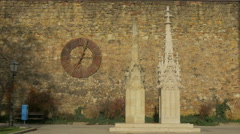 Man passing by a rusty clock and church tower tops at Zagreb Cathedral - stock footage