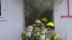 Smoke billows out of doorway of burning house - stock footage