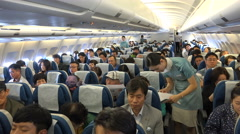Flight attendants, cabin crew, airline passengers, on board, flying Korean Air Stock Footage