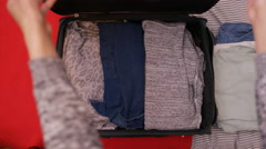 4K Overhead view, the hands of unrecognizable woman packing luggage for a trip Arkistovideo