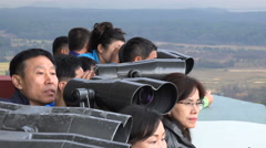 South Korean tourists use binoculars to look at the North Korea border Stock Footage
