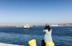 Woman taking photos of the bay of San Diego while sitting down at pier Stock Photos