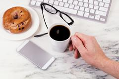 Morning coffee while working at home on white marble countertop - stock photo